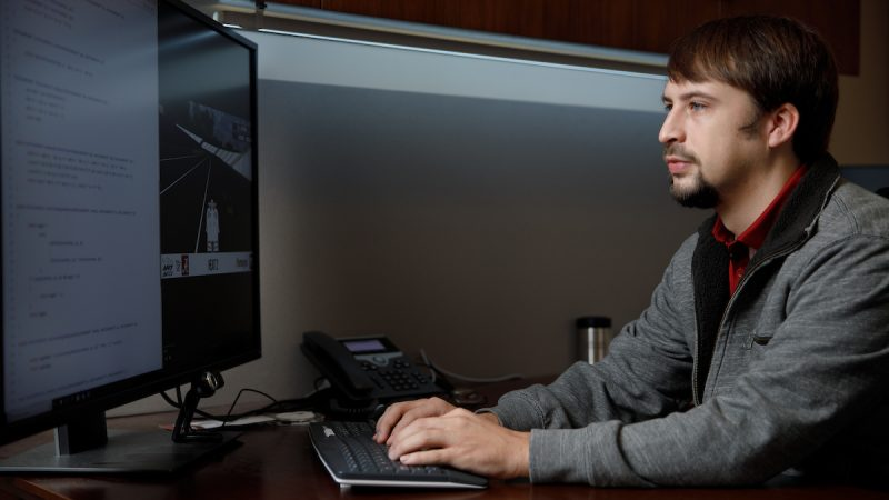 A man works on a computer with two monitors.