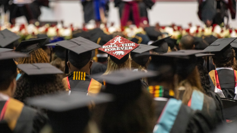 Students wearing mortar boards at a commencement ceremony. One mortar board says Roll Tide always.