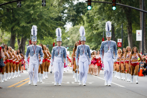 Drum majors lead the Million Dollar Band as they march down a street