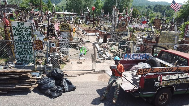 A man on the tailgate of a pickup truck sits before his yard of scultpures.