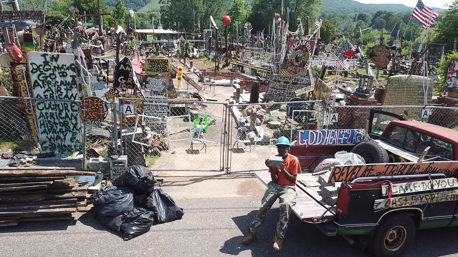 A man on the tailgate of a pickup truck sits before his yard of sculptures.