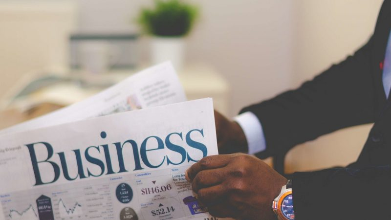 Photo by nappy from Pexels shows a man in a suit reading the business section of a newspaper.